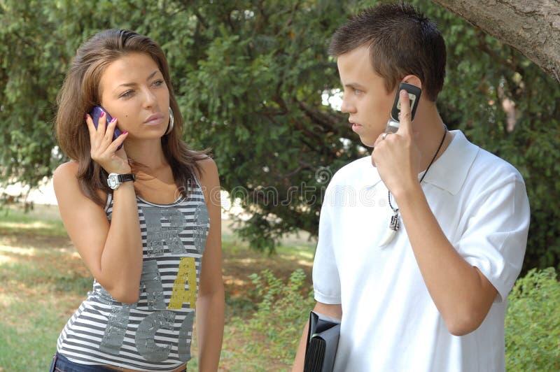 Junge Paare mit Mobiles lizenzfreie stockbilder