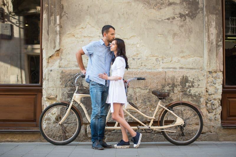 Junge Paare mit Retro- Tandemfahrrad an der Straßenstadt stockfoto