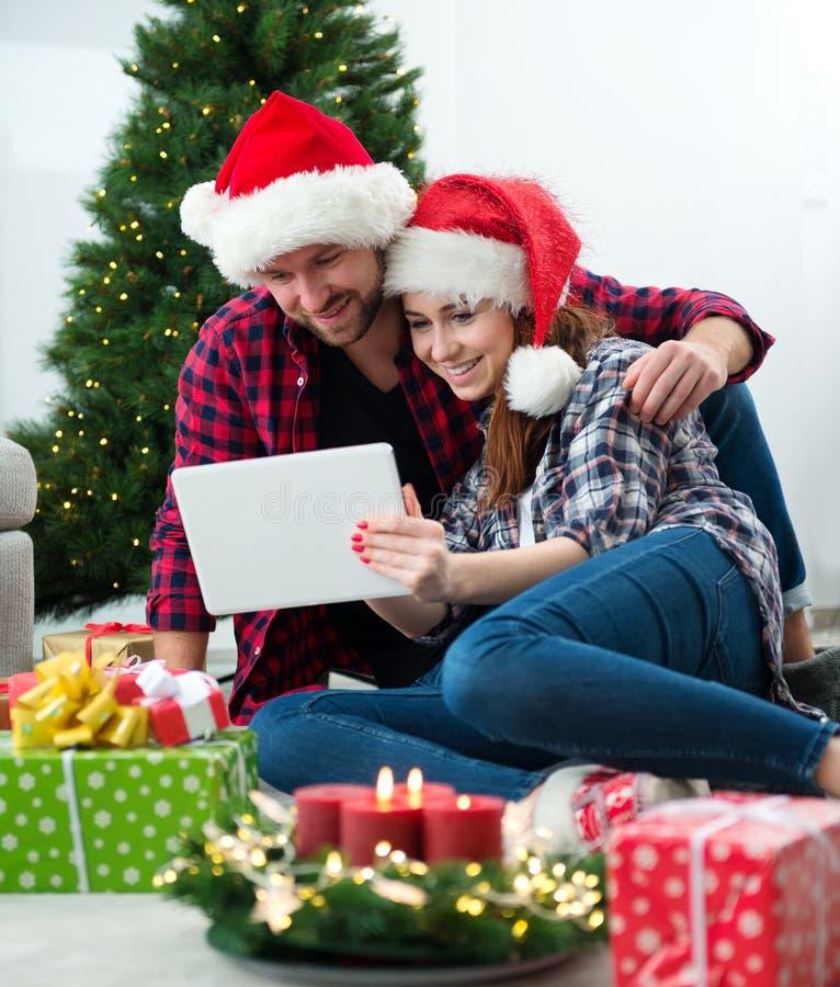 Junge Paare mit Santa Claus-Hüte kaufendem on-line-Weihnachtsgif lizenzfreie stockbilder