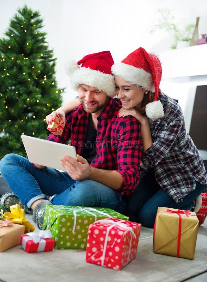 Junge Paare mit Santa Claus-Hüte kaufendem on-line-Weihnachtsgif lizenzfreie stockfotos