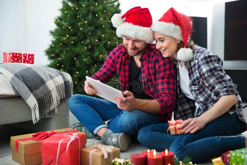 Junge Paare mit Santa Claus-Hüte kaufendem on-line-Weihnachtsgif lizenzfreie stockfotografie