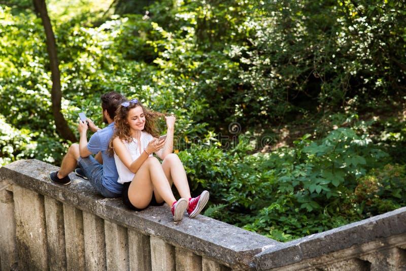 Junge Paare mit Smartphones in der Stadt, die auf Betonmauer sitzt lizenzfreie stockbilder