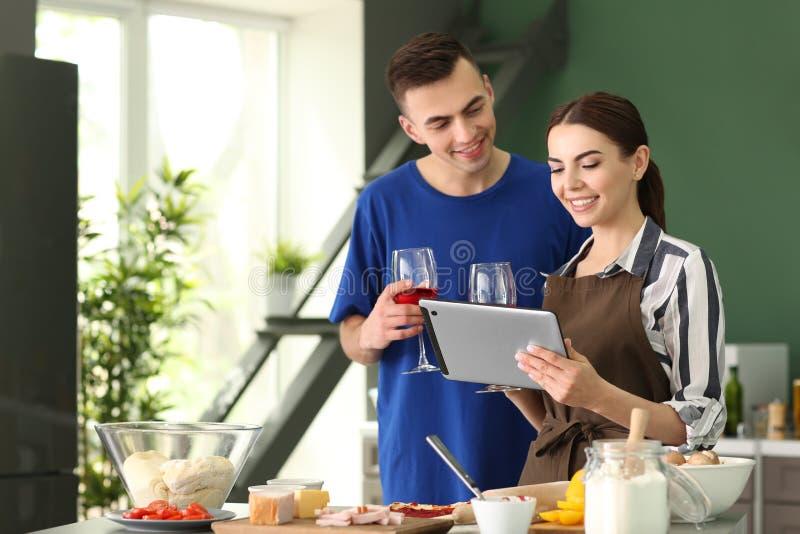 Junge Paare mit Tablette Ablesenpc-Rezepten in der Küche stockfotos