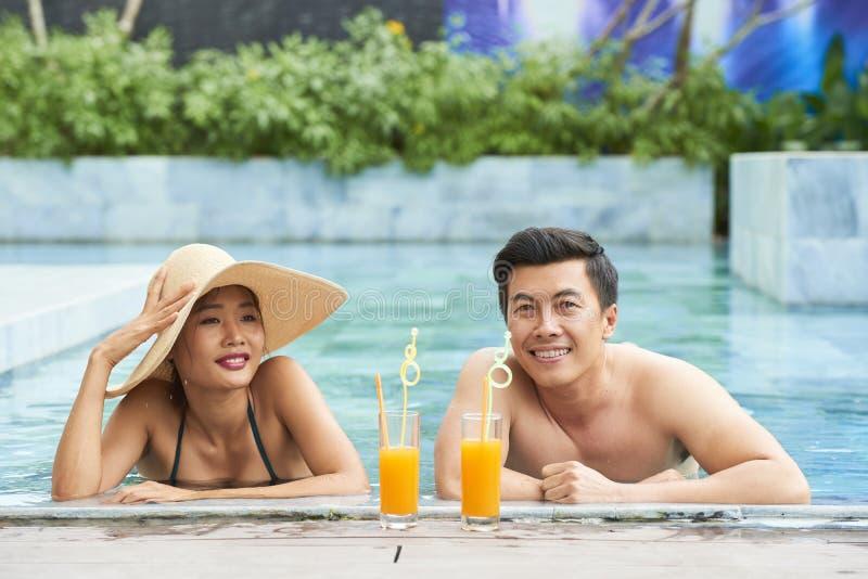 Junge Paare nahe dem Poolside lizenzfreie stockbilder
