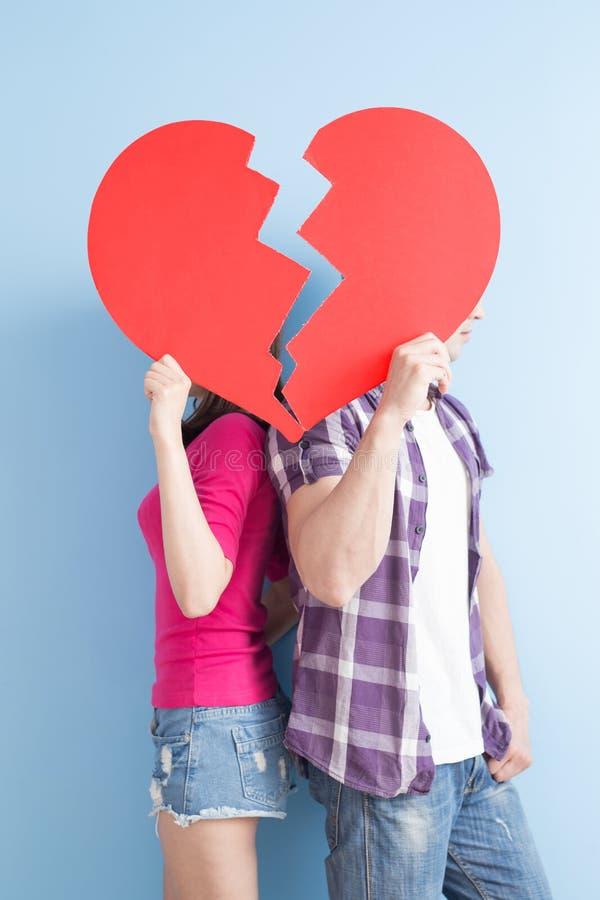 Junge Paare nehmen defektes Herz lizenzfreie stockbilder