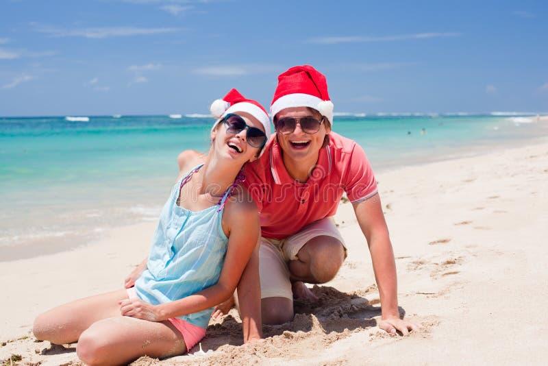 Junge Paare in Sankt-Hüten, die auf tropischem lachen lizenzfreies stockbild