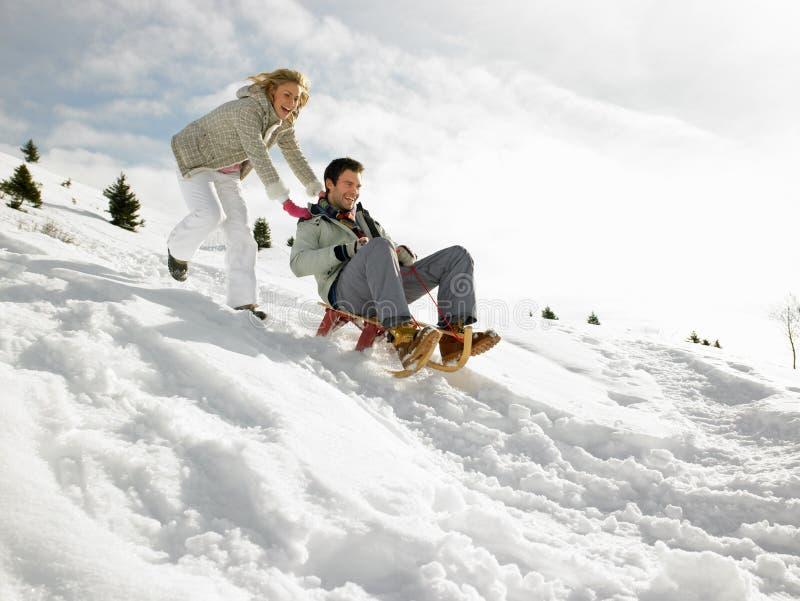 Junge Paare Sledding lizenzfreies stockfoto