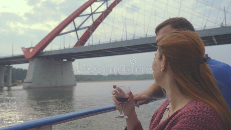 Junge Paare stehen auf einer Yacht, Getränkwein auf dem Brückenhintergrund still lizenzfreie stockfotografie