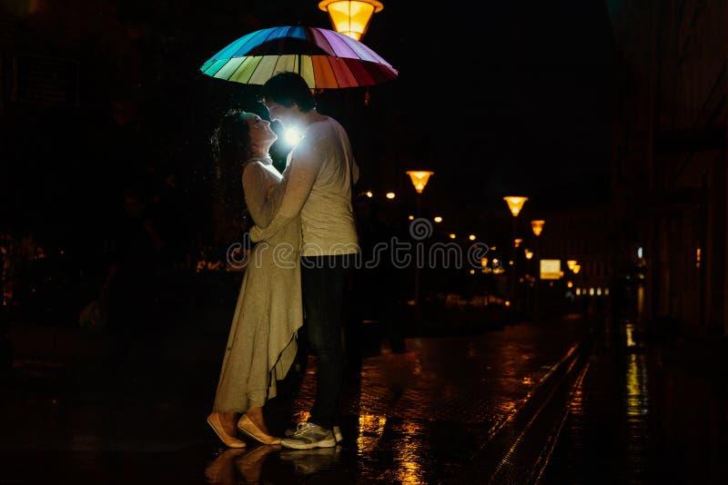 Junge Paare unter Küssen eines Regenschirmes nachts auf einer Stadtstraße stockbild