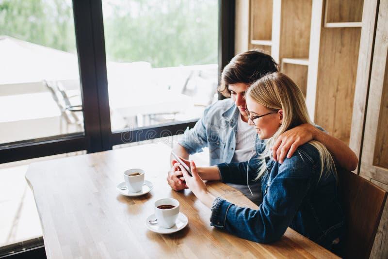 Junge Paare unter Verwendung der Tablette beim am Café zusammen sitzen stockfotos