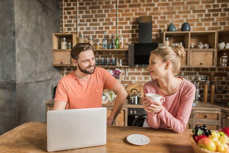 Junge Paare unter Verwendung des Laptops, in der Küche und in sich lächeln stockbild