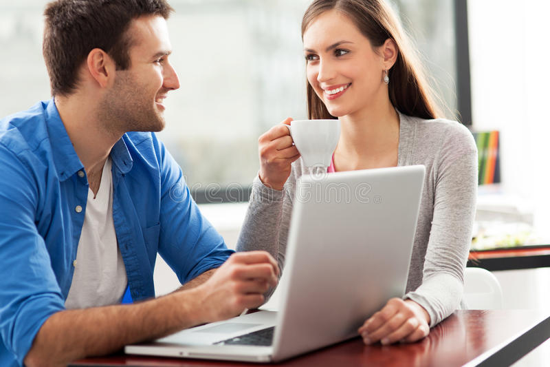 Paare, die Laptop am Café sprechen und verwenden lizenzfreie stockfotos