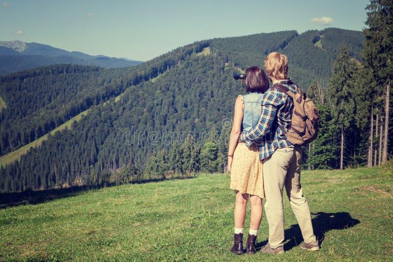Junge Paare von den Reisenden, die Bergblick genießen lizenzfreies stockbild