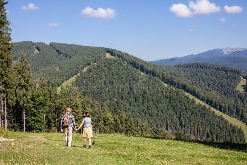 Junge Paare von den Reisenden, die Bergblick genießen lizenzfreies stockfoto