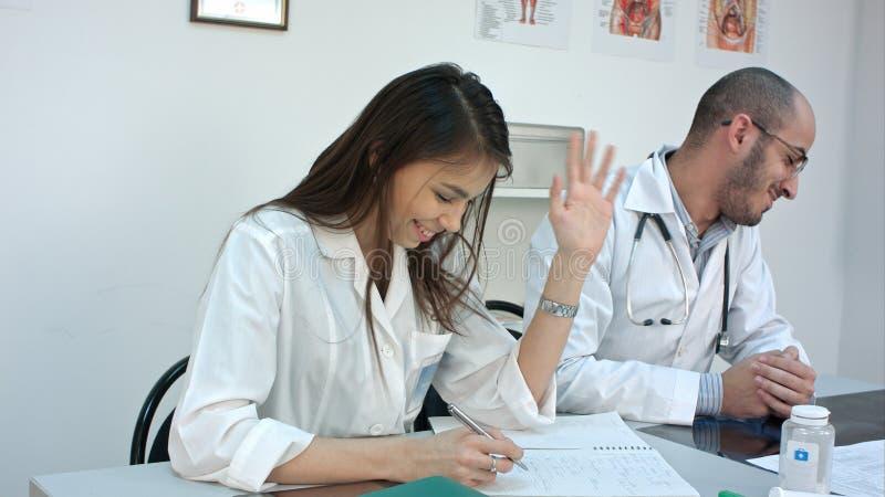 Junge Paare von Doktor und von Krankenschwester, die über einander nach einem Streit lachen stockbild