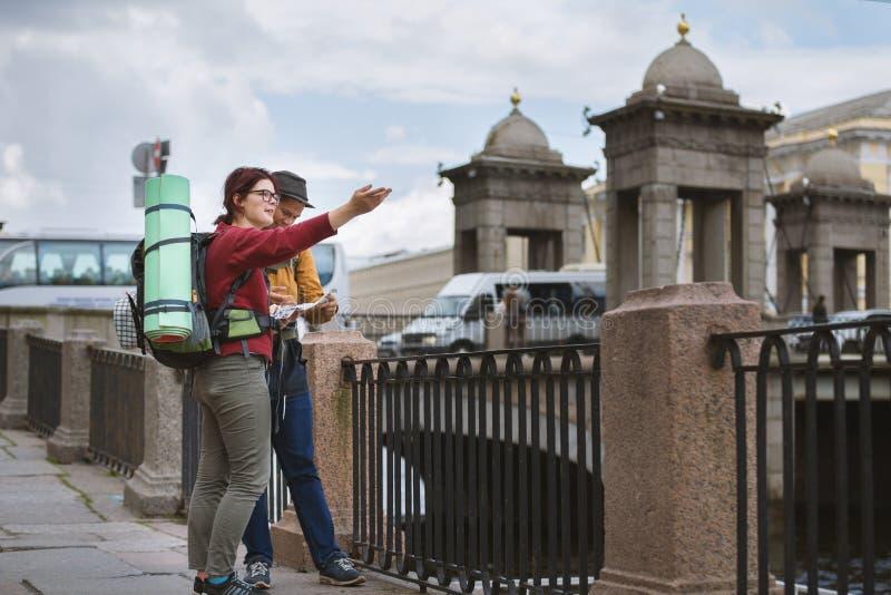 Junge Paare von Touristen überprüfen den Weg auf dem Navigator stockfoto