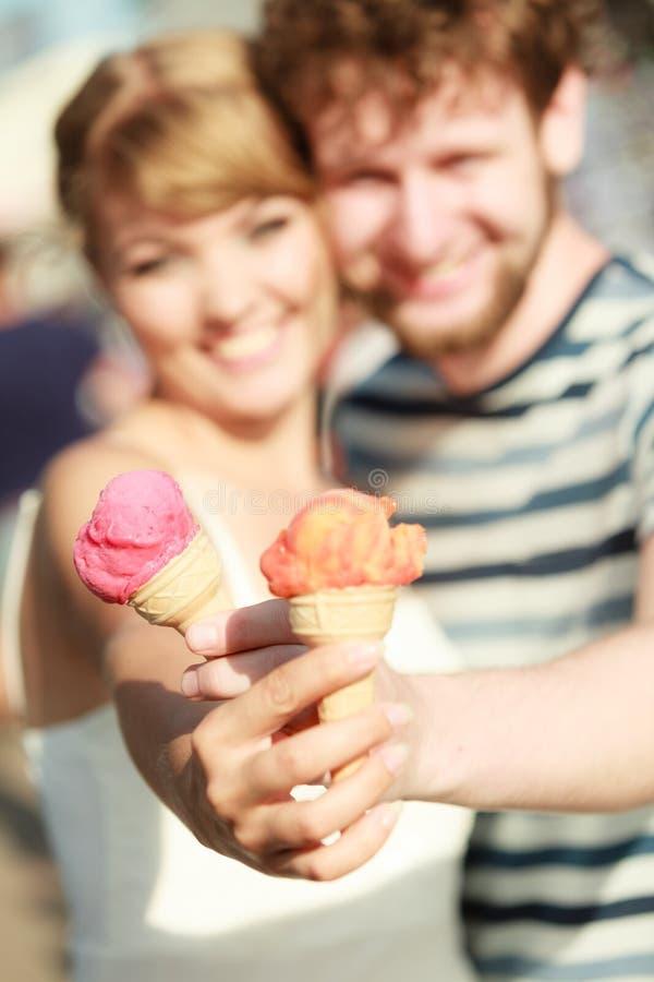 Junge Paare, welche die Eiscreme im Freien essen lizenzfreies stockbild