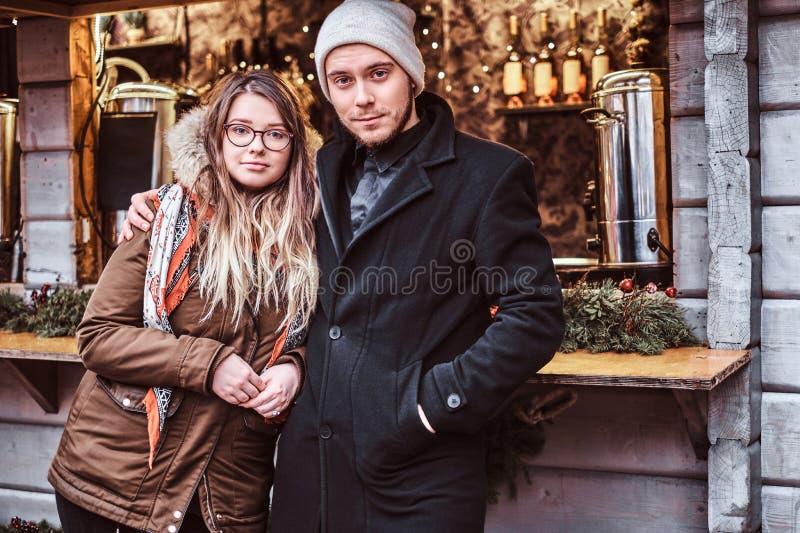 Junge Paare, welche die Kamera bei der Stellung nahe dem Zähler mit Andenken am Winter Weihnachten umarmen und betrachten lizenzfreie stockfotos
