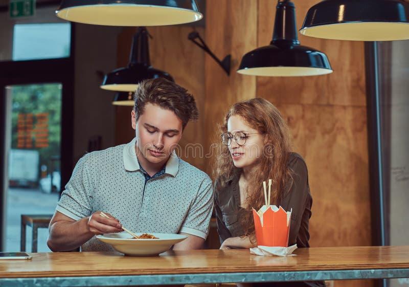 Junge Paare, welche die zufällige Kleidung isst würzige Nudeln in einem asiatischen Restaurant tragen lizenzfreies stockfoto