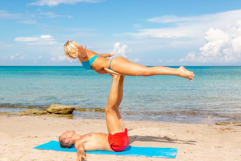Junge Paarfrau und -männer auf dem Strand, der zusammen Eignungsyogaübung tut Acroyoga-Element für Stärke und Balance stockfotografie