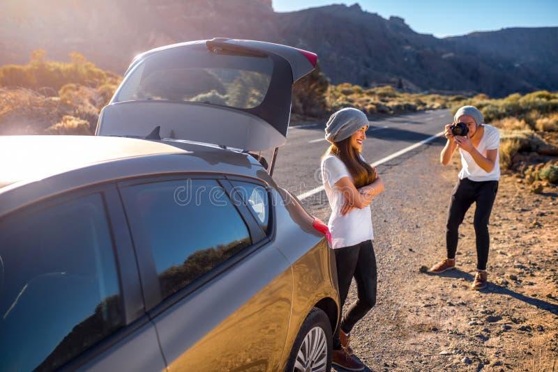 Junge Paarreisende, die Spaß nahe dem Auto haben lizenzfreie stockfotos