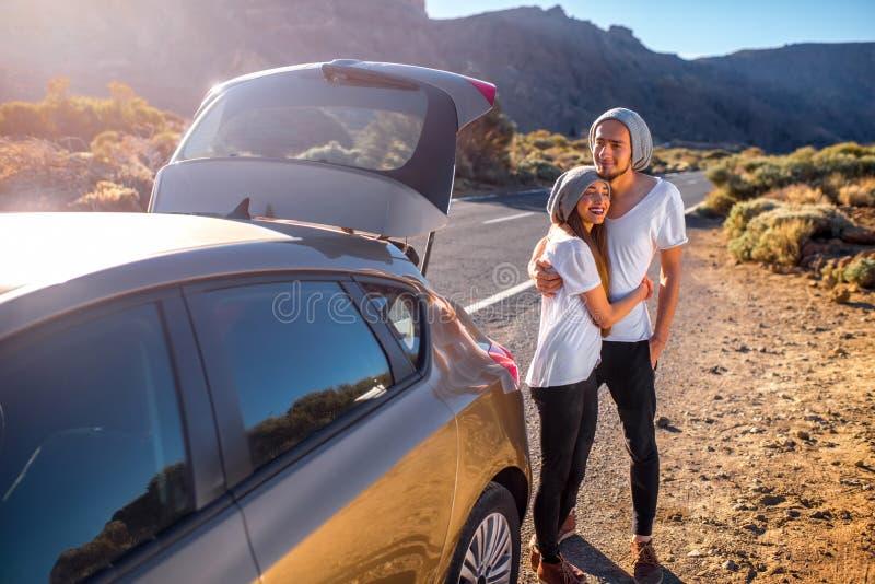 Junge Paarreisende, die Spaß nahe dem Auto haben lizenzfreies stockbild