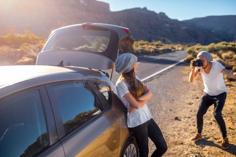 Junge Paarreisende, die Spaß nahe dem Auto haben stockfotos