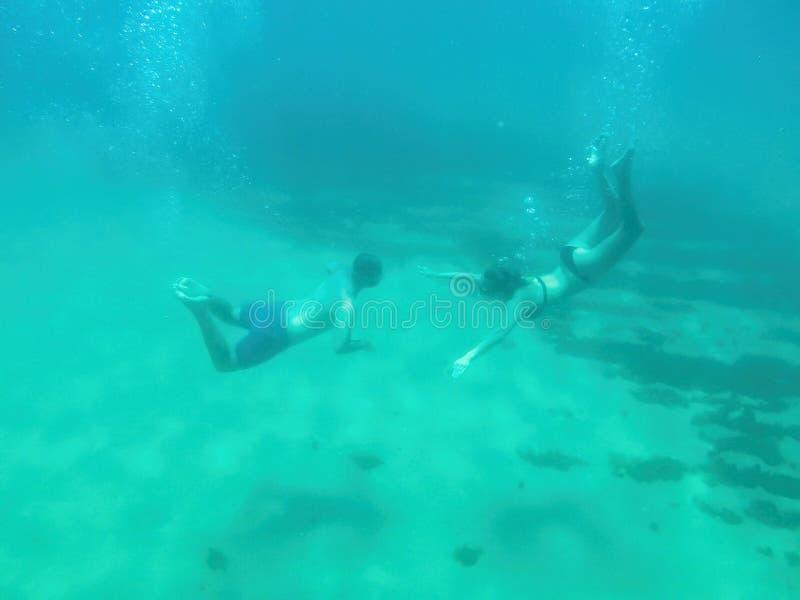 Junge Paarschwimmen in einem transparenten Ozeanwasser in Spanien lizenzfreies stockbild