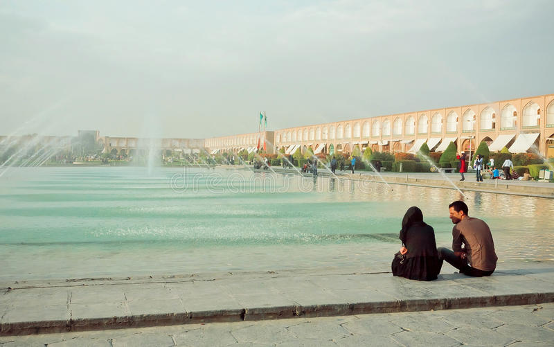 Junge Paarsitzung und Unterhaltung nahe einem Brunnen des populären Imams Square in Isfahan stockfotos