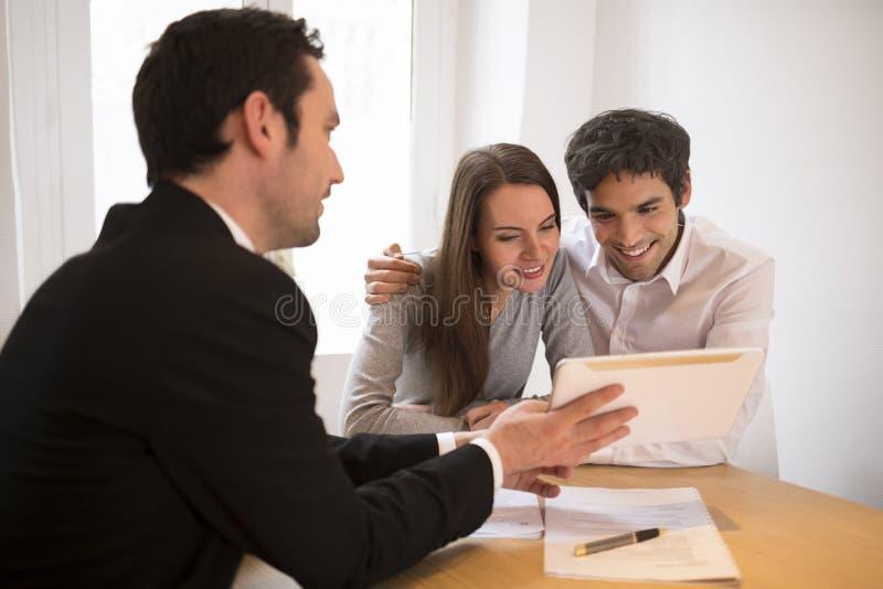 Junge Paarsitzungsimmobilienagentur, zum des Eigentums, presenta zu kaufen lizenzfreies stockbild