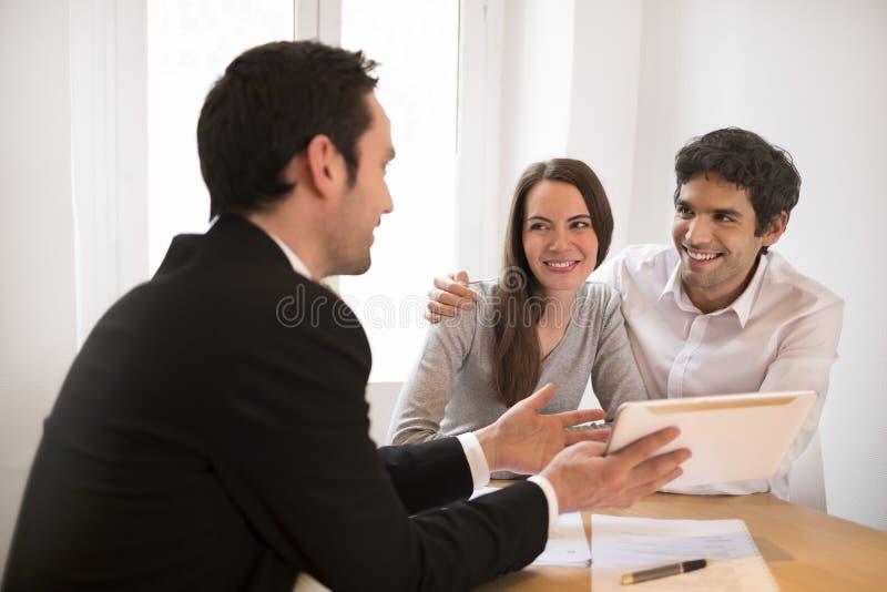 Junge Paarsitzungsimmobilienagentur, zum des Eigentums, presenta zu kaufen stockbilder