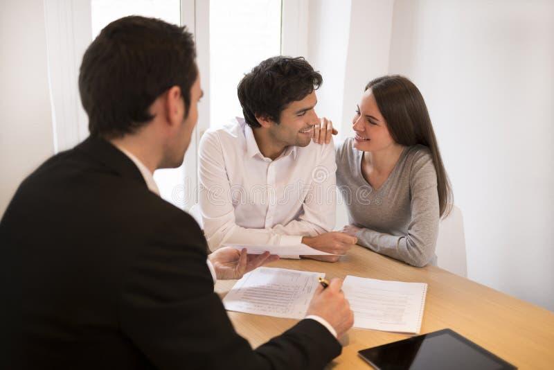 Junge Paarsitzungsimmobilienagentur, zum des Eigentums zu kaufen stockbild