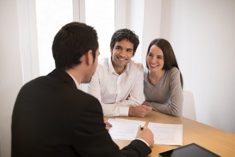 Junge Paarsitzungsimmobilienagentur, zum des Eigentums zu kaufen lizenzfreie stockbilder