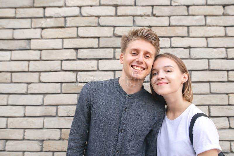 junge Paarstellung auf der Wand einer Backsteinmauer, die Kamera und das Lächeln betrachtend stockfotografie