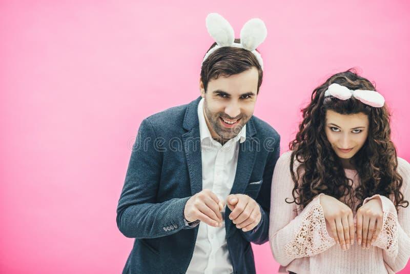 Junge Paarstellung auf rosa Hintergrund Mit den Ohren eines Häschens auf dem Kopf Schön, Macho- oder Freund und nettes Mädchen stockfoto