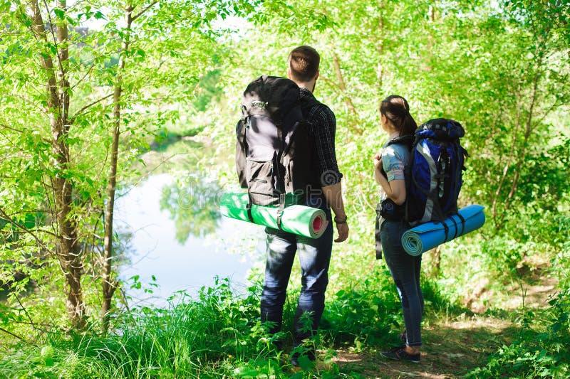 Junge Paarwanderer im Wald trägt Mann und Frau mit Rucksäcken auf Straße in der Natur zur Schau stockfoto