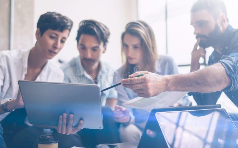 Junge Partner, die Forschung für neue Geschäftsrichtung machen Junger Geschäftsmann, der modernen Laptop bearbeitet und Dokumente lizenzfreie stockfotos