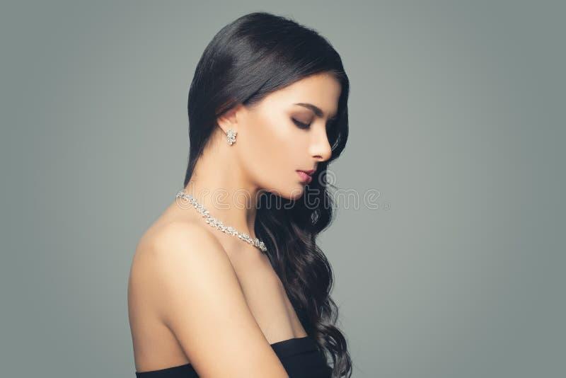 Junge perfekte brunette Frau mit Diamantschmuckhalskette und -ohrringen auf grauem Hintergrund lizenzfreie stockfotografie