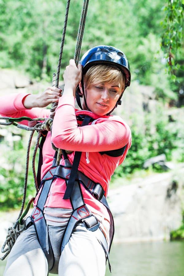 Junge perfekte Frau, die auf eine Ziplinie schiebt lizenzfreies stockbild