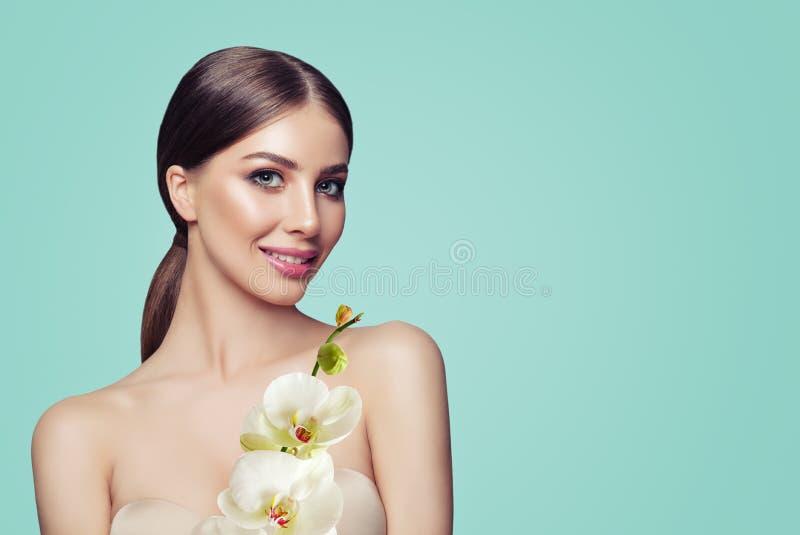 Junge perfekte Frau mit Make-up und Orchideen-Blumen stockbild