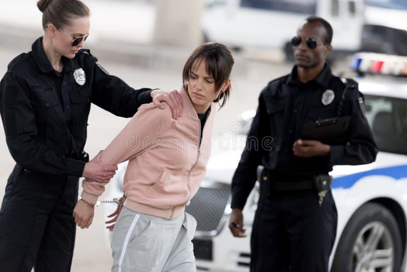 junge Polizeibeamtin, die weiblichen Verbrecher in den Handschellen während Partnerstellung hält stockfotografie
