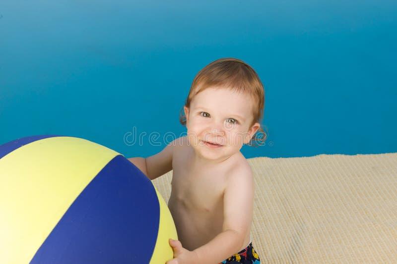 Junge am Pool mit Wasserball lizenzfreies stockfoto