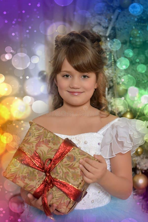 Junge Prinzessin im Weiß mit einem blauen eleganten Kleid mit einem Geschenk herein lizenzfreie stockbilder