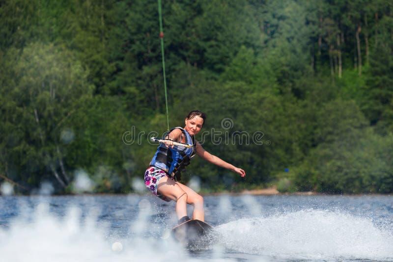 Junge recht d?nnes Brunettefrauen-Reiten-wakeboard auf Welle von mot lizenzfreie stockbilder