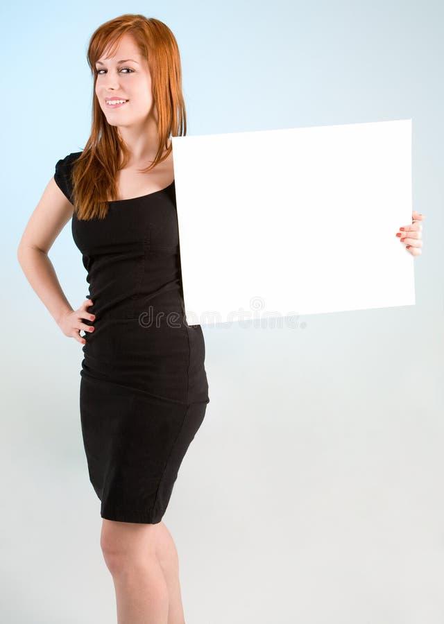 Junge Redhead-Frau, die ein unbelegtes weißes Zeichen anhält stockfoto