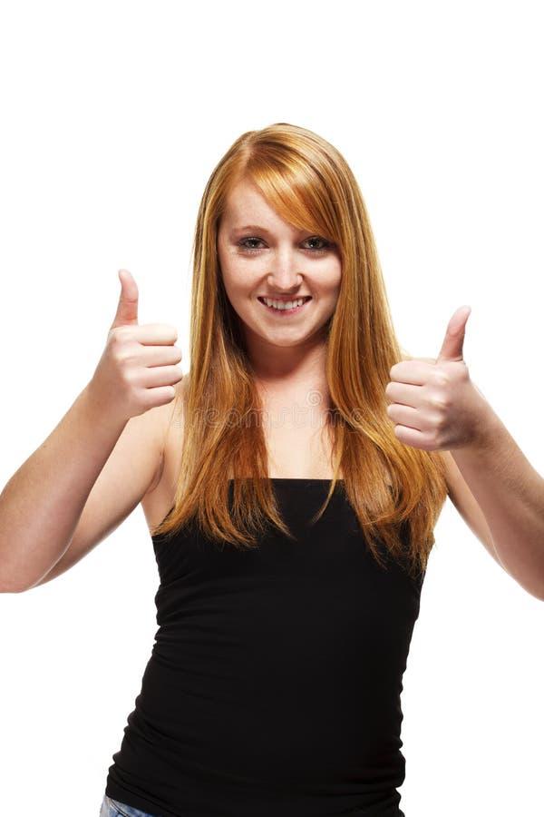 Junge Redheadfrau, die sich zwei Daumen zeigt stockfotos