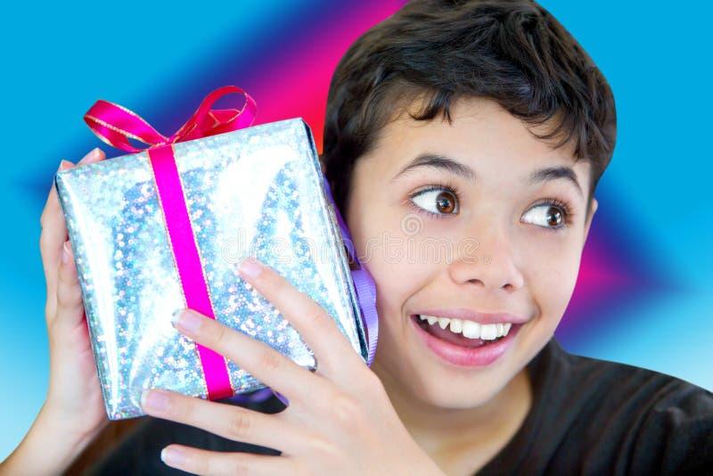 Junge regte das Halten eines eingewickelten oben Weihnachtsgeschenks auf stockbilder