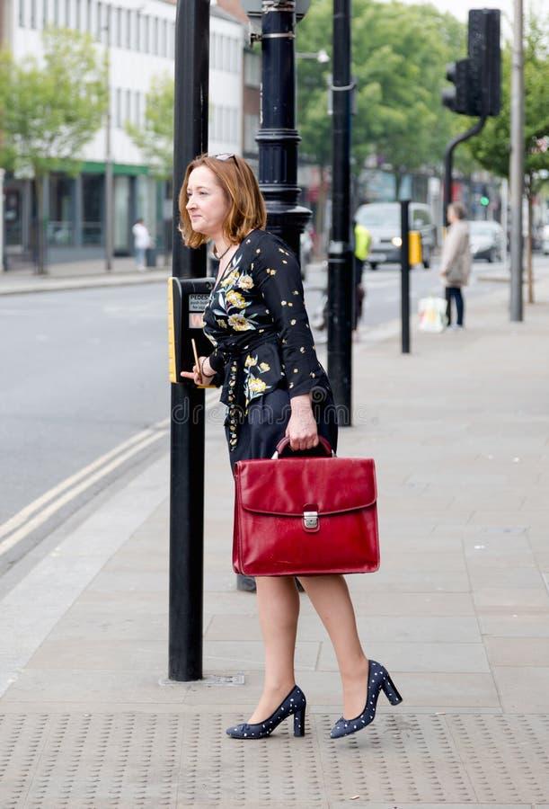 Junge reife Geschäftsfrau steht auf Fußgängerübergang pressin stockfoto