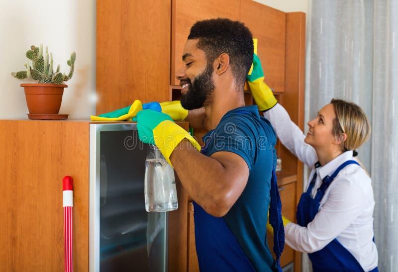 Junge Reiniger, die im gewöhnlichen Haus säubern und abwischen stockbilder
