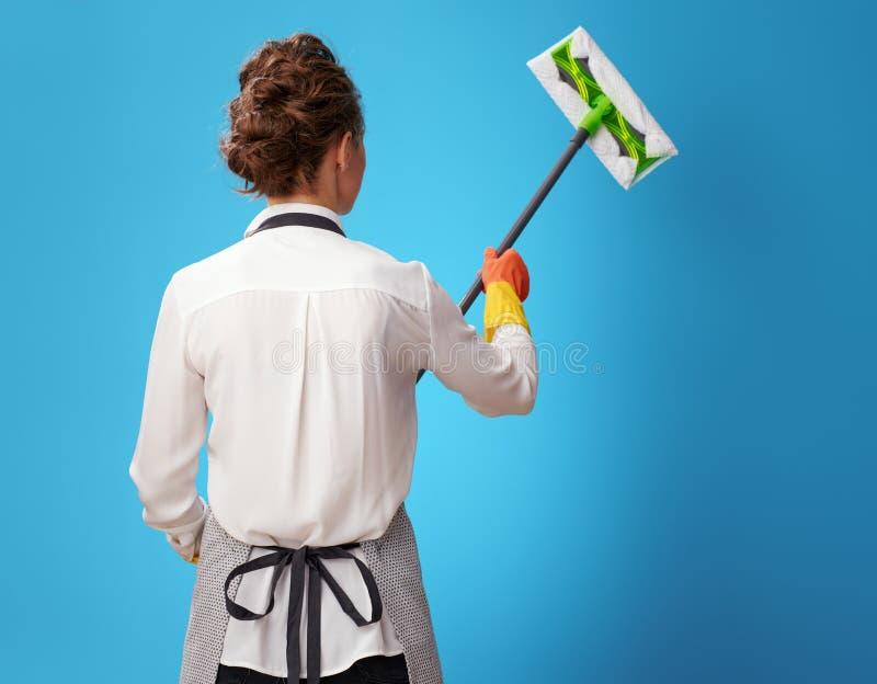 Junge Reinigungsfrau im Schutzblech unter Verwendung des Mops auf Blau stockfotografie
